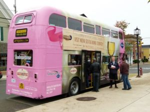 The Magic Winery Bus, a pink English double-decker bus that drives the Hop-On, Hop-Off vineyard route in Annapolis Valley each autumn