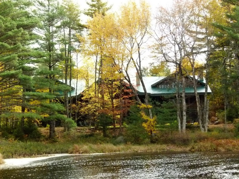 A view of Trout Point Lodge's main building from across the river through colourful autumn foliage.