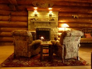 One of Trout Point Lodge's fireplaces with comfy armchairs and a side table.