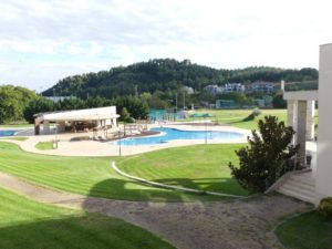 Elpida's outdoor swimming pool is surrounded by a park-like setting.