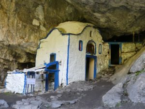 The tiny, white and blue chapel of St Dionysiossits under a rock jutting out overhead giving the impression of a shallow cave.