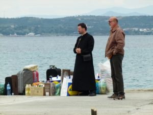A monk and male visitor await a boat out to a monastery