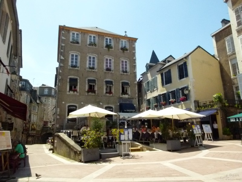 Tables with sun umbrellas fill the plaza outside a restaurant in the old quarter in Pau