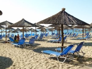 Soft sand beach with straw umbrellas and lounge chairs
